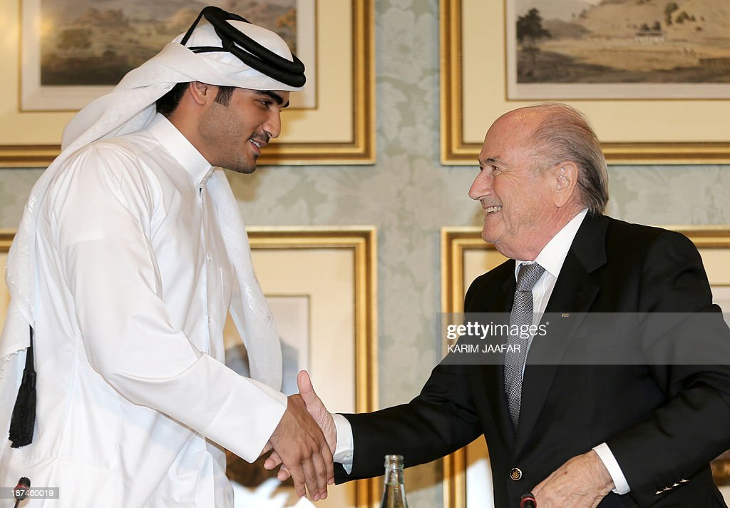 Chairman of the Qatar 2022 bid committee Sheikh Mohammed bin Hamad al-Thani (L) shakes hands with FIFA president <a gi-track='captionPersonalityLinkClicked' href=/galleries/search?phrase=Sepp+Blatter&family=editorial&specificpeople=209372 ng-click='$event.stopPropagation()'>Sepp Blatter</a> during a press conference in the Qatari capital Doha on November 9, 2013. Blatter confirmed on November 8 that he would favour playing the controversial 2022 Qatar World Cup in November and December.