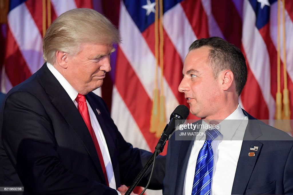 Chairman of the Republican National Committee (RNC) Reince Priebus (R) shakes hands with Republican presidential elect Donald Trump (L) during election night at the New York Hilton Midtown in New York on November 9, 2016. / AFP / JIM
