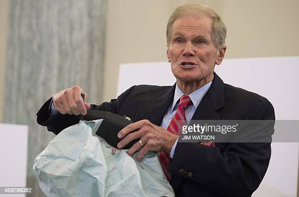 Chairman of the US Senate Committee on Commerce Science and Transportation Bill Nelson DFL holds up a defective airbag with holes torn through it on...