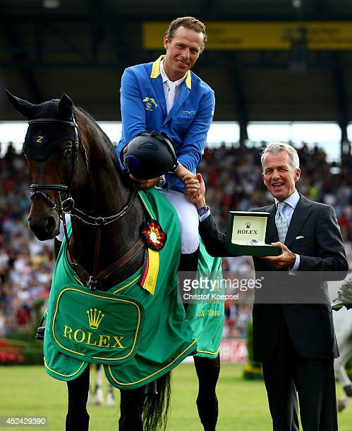 Chairman Peter Streit of Rolex Germany honours Christian Ahlmann of Germany rides on Codex One winning the Rolex Grand Prix jumping competition...