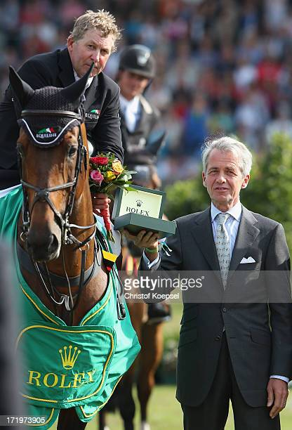 Chairman Petr Streit of Rolex Germany hands out the winning price to Nick Skelton of GreatBritain riding on Big Star on the podium during the Rolex...
