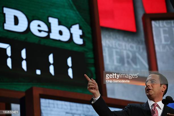 Chairman Reince Priebus points to a display showing the national debt at the start of the Republican National Convention at the Tampa Bay Times Forum...