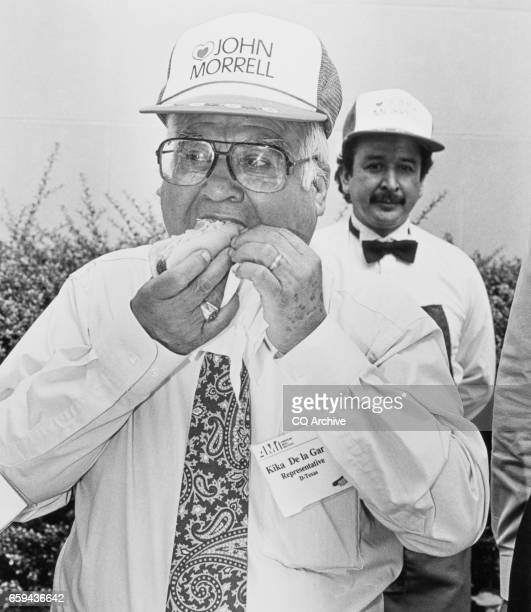 Chairman Rep Kika de la Garza DTex eating a 'John Morrell' hot dog at the AMI hot dog cookout during National Hotdog Month on July 24 1992