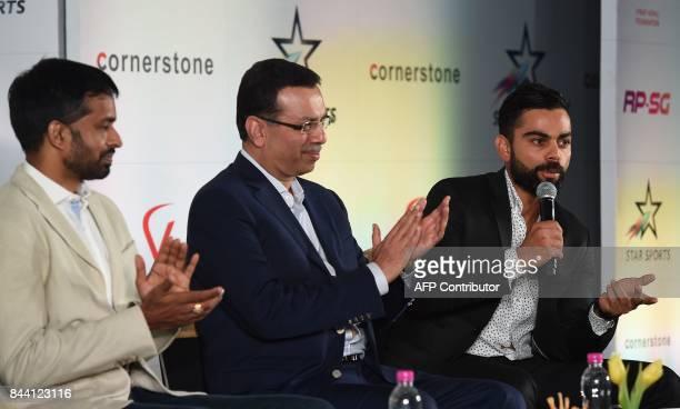 Chairman RPSG group Sanjiv Goenka and Chief National Coach for the Indian Badminton team Pullela Gopichand applaud as India Cricketer Virat Kohli...