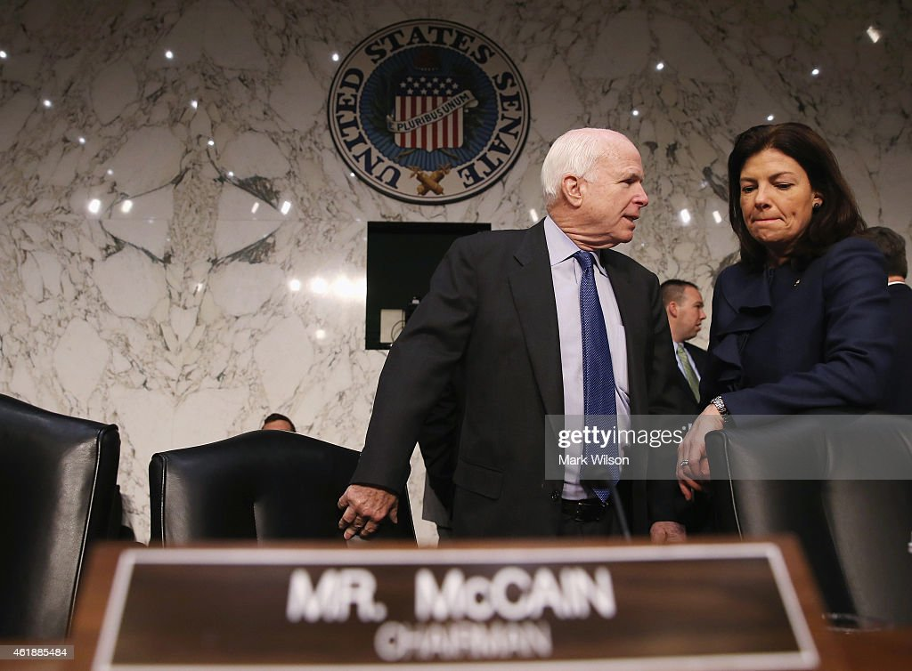 Chairman Sen. John McCain (R-AZ) talks with U.S. Sen. Kelly Ayotte (R-NH) before the start of a Senate Armed Services Committee hearing on Capitol Hill, January 21, 2015 in Washington, DC. The committee heard testimony on from former cabinet officials regarding global challenges and United States national security strategy.
