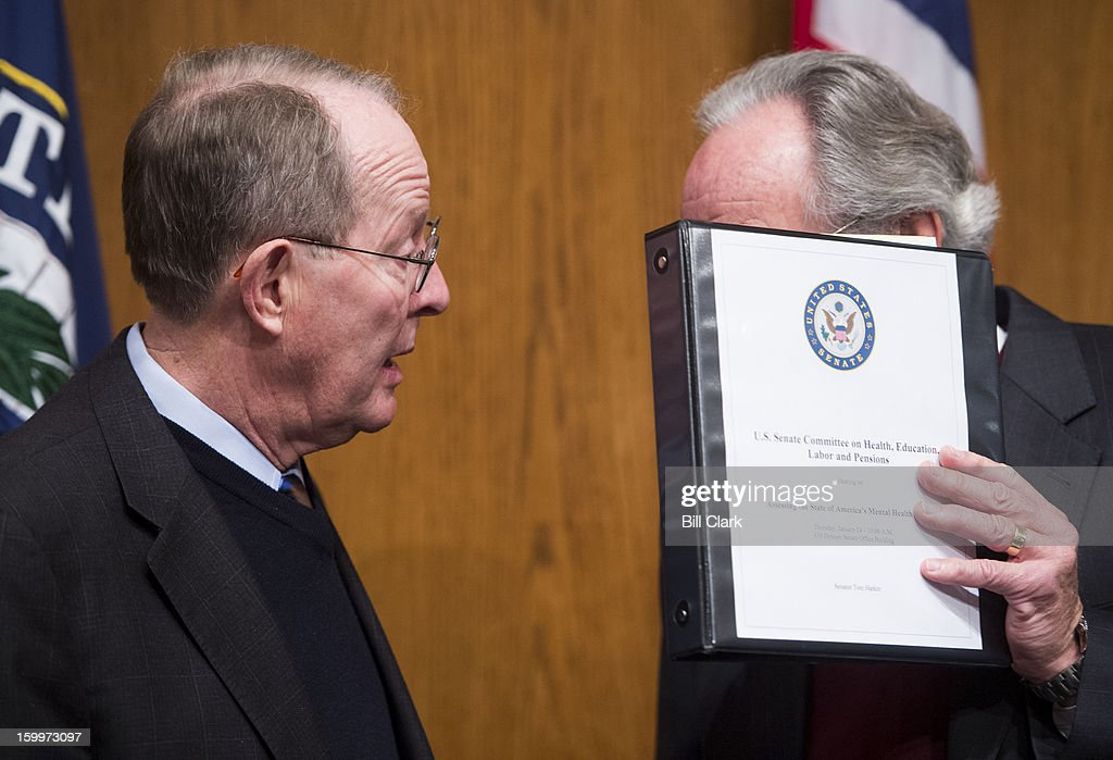Chairman Tom Harkin, D-Iowa, right, holds up a notebook to shield his conversation with Sen. Lamar Alexander, R-Tenn., during the Senate Health, Education, Labor and Pensions Committee hearing on 'Assessing the State of America's Mental Health System' in the Dirksen Senate Office Building on Thursday, January 24, 2013.