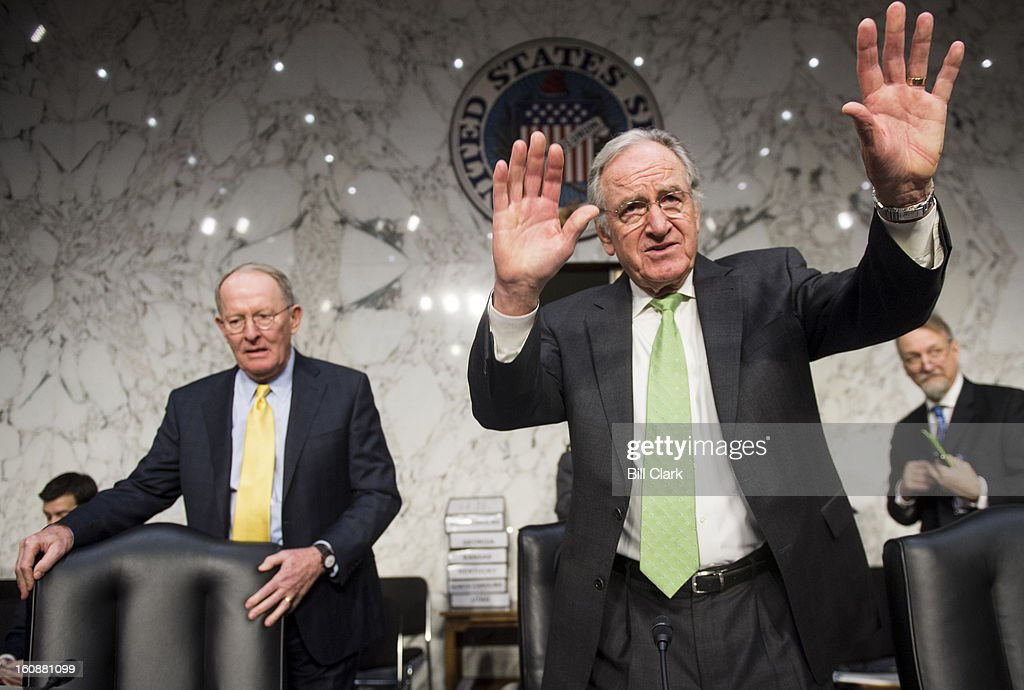 Chairman Tom Harkin, D-Iowa, right, tries to quiet a CodePink protester calling for passage of the Employment Non-Discrimination Act before the start of the Senate Health, Education, Labor and Pensions Committee hearing on 'No Child Left Behind: Early Lessons from State Flexibility Waivers' on Thursday, Feb. 7, 2013. Sen. Lamar Alexander, R-Tenn., left, takes his seat.