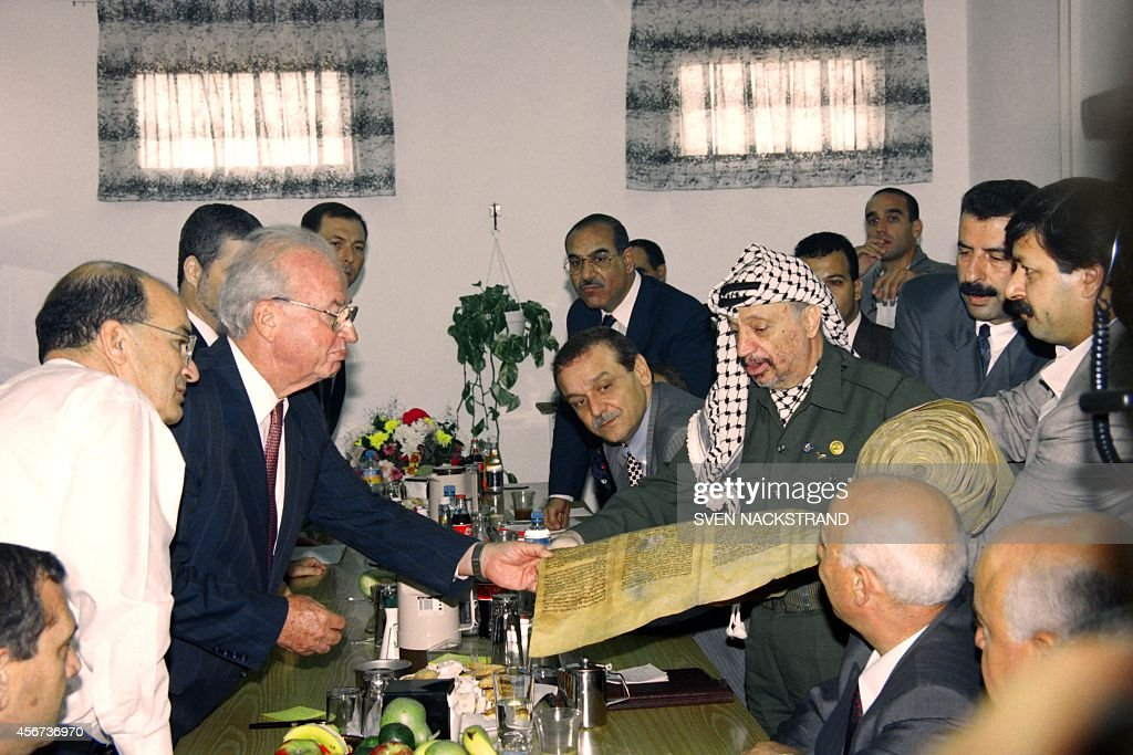 PLO Chairman <a gi-track='captionPersonalityLinkClicked' href=/galleries/search?phrase=Yasser+Arafat+-+Politiek+leider&family=editorial&specificpeople=118625 ng-click='$event.stopPropagation()'>Yasser Arafat</a> (R) gives to Israeli Prime Minister <a gi-track='captionPersonalityLinkClicked' href=/galleries/search?phrase=Yitzhak+Rabin&family=editorial&specificpeople=94269 ng-click='$event.stopPropagation()'>Yitzhak Rabin</a> an ancient scroll of the Jewish 'Torah' or law from Yemen on September 25, 1994 during their meeting at Erez checkpoint. Rabin and Arafat agreed to launch negotiations a week on the next stage of Autonomy, including army redeployment and elections.
