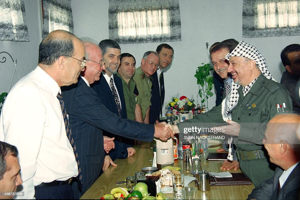 PLO Chairman <a gi-track='captionPersonalityLinkClicked' href=/galleries/search?phrase=Yasser+Arafat+-+Politiek+leider&family=editorial&specificpeople=118625 ng-click='$event.stopPropagation()'>Yasser Arafat</a> (R) shakes hand with Israeli Prime Minister <a gi-track='captionPersonalityLinkClicked' href=/galleries/search?phrase=Yitzhak+Rabin&family=editorial&specificpeople=94269 ng-click='$event.stopPropagation()'>Yitzhak Rabin</a> after giving to him an ancient scroll of the Jewish 'Torah' or law from Yemen on September 25, 1994 during their meeting at Erez checkpoint. Rabin and Arafat agreed to launch negotiations a week on the next stage of Autonomy, including army redeployment and elections.