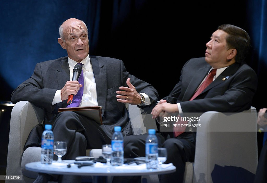 Chairman/Co-founder of the Chertoff Group, and Former Secretary at the US Department of Homeland Security Michael Chertoff (L) speaks next to Singapore President of the Forum's Coordination association, and Senior Deputy Secretary Ministry of Home Affairs Khoo Boon Hui, during the opening plenary session of an Interpol international forum on Technology Against Crime (TAC) on July 8, 2013, in Lyon, southeastern France.