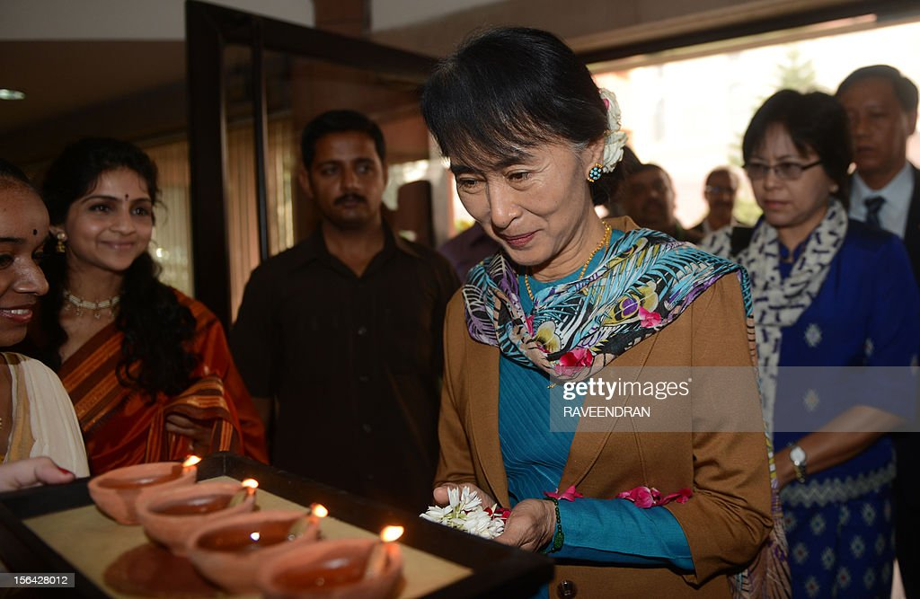 Chairperson and Oppostion leader of The National League for Democracy of Myanmar, Aung San Suu Kyi (C) is welcomed with flowers and an oil lamp at Parliament House in New Delhi on November 15, 2012, ahead of a meeting with Speaker of the Indian Parliament Meira Kumar. Suu Kyi is in India for a seven day visit. AFP PHOTO/RAVEENDRAN