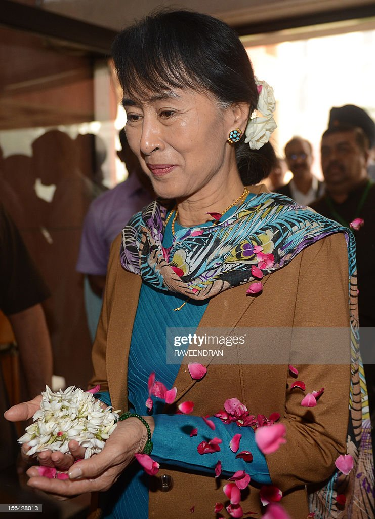 Chairperson and Oppostion leader of The National League for Democracy of Myanmar, Aung San Suu Kyi (C) is welcomed with flowers at Parliament House in New Delhi on November 15, 2012, ahead of a meeting with Speaker of the Indian Parliament Meira Kumar. Suu Kyi is in India for a seven day visit.