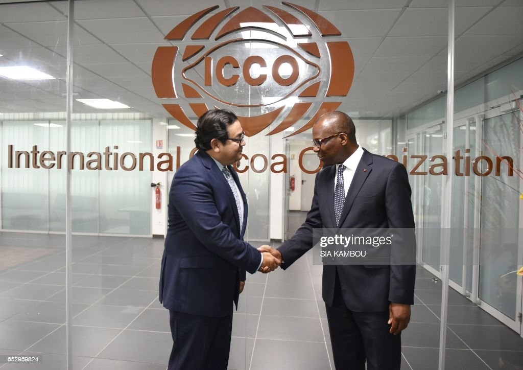 Chairperson of the International Cacao Organization (ICCO) Luis Valverde (L) shakes hands with ICCO Executive Director Jean-Marc Anga at the new headquarters of the ICCO in Abidjan on March 13, 2017. The headquarters of the ICCO, based in London for over half a century, have been relocated to Abidjan, the world's largest cocoa producer. / AFP PHOTO / Sia KAMBOU