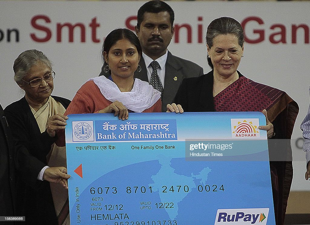 UPA chairperson Sonia Gandhi and Delhi Chief Minister Sheila Dikshit giving away an Aadhar enabled card (for withdrawing money from any ATM) during the launch of the Delhi Annshree Yojana on December 15, 2012 in New Delhi, India. Under the scheme monthly cash subsidy of Rs 600 will be transferred directly into bank account of senior-most female member of two lakh poor families.