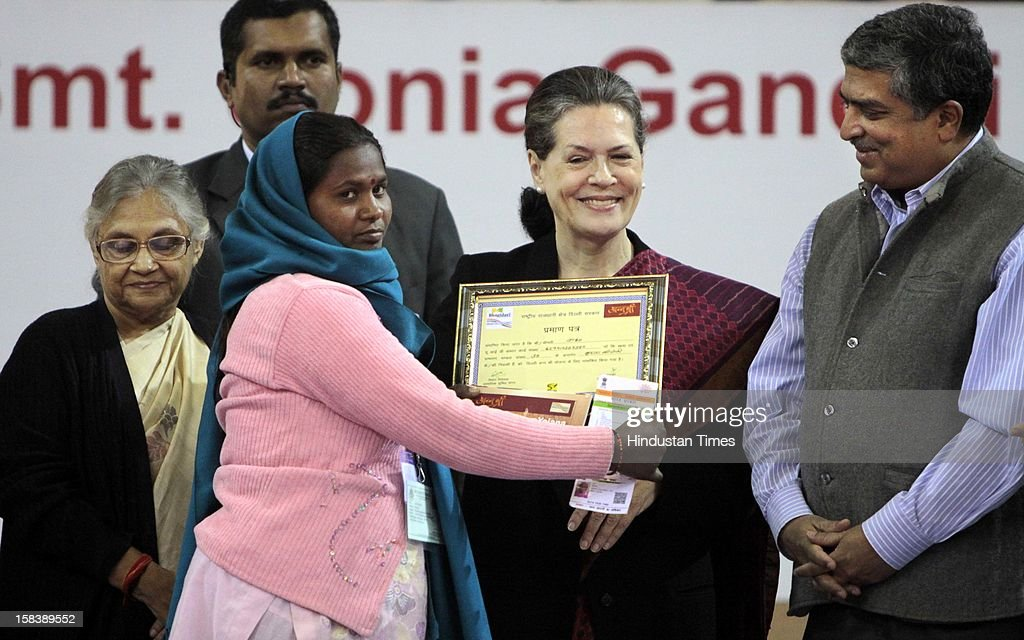 UPA chairperson Sonia Gandhi, Delhi Chief Minister Sheila Dikshit and UIDAI Chairman Nandan Nilekani giving away an Aadhar enabled card (for withdrawing money from any ATM) during the launch of the Delhi Annshree Yojana on December 15, 2012 in New Delhi, India. Under the scheme monthly cash subsidy of Rs 600 will be transferred directly into bank account of senior-most female member of two lakh poor families.