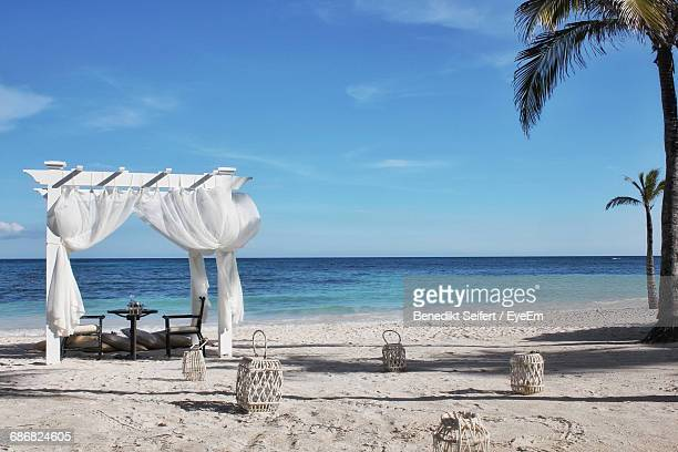Chairs And Canopy On Beach Against Sky During Sunny Day