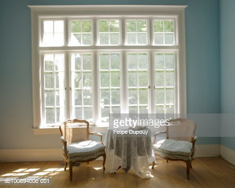 Chairs and table by bright window with open book on table : Photo