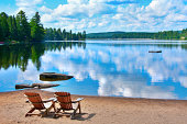 two wooden deck chairs on the shore of a lake in Canada with clouds reflecting on the water