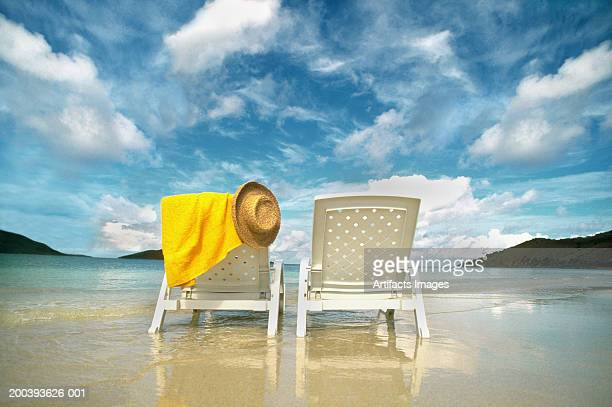 Chairs on beach with towel and hat
