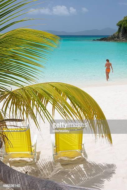 Liegestühle unter Palmen an einem tropischen Strand am Karibischen Meer