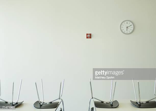 Chairs upside down on tables and clock on wall