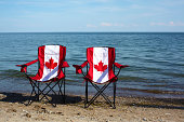 Folding chairs with Canadian flag on them by the lake. Lake Ontario, Canada. Idyllic scene. Summer in Canada. Vacationing in Canada. Canada Day. Lakeshore. Summer. Vacation.