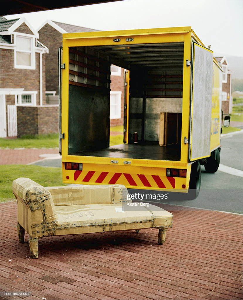 Chaise longue wrapped in cardboard on driveway by open truck