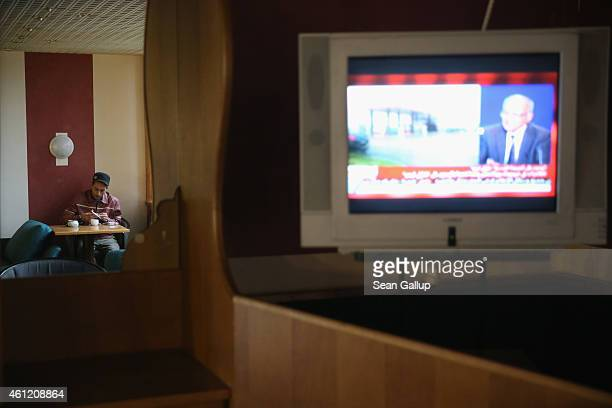 Chakib Rahali a refugee from Tunisia smokes a cigarette as a television shows a French Arabiclanguage news program in the recreation room at the...