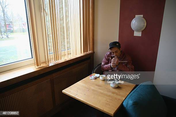 Chakib Rahali a refugee from Tunisia smokes a cigarette in the television room at the Spreehotel refugee center on January 8 2015 in Bautzen Germany...