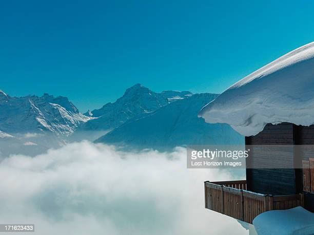 Chalet covered in snow in mountains