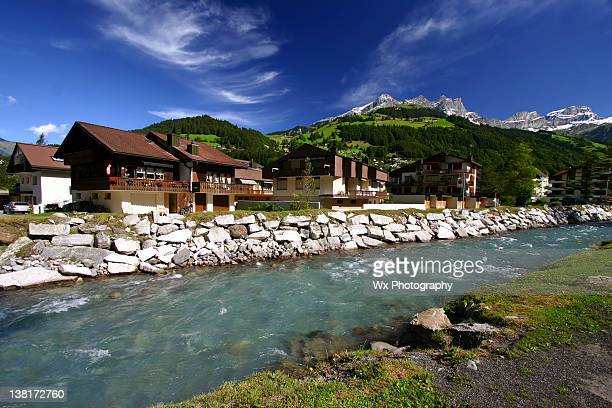 Chalets along creek in Swiss Alps during summer