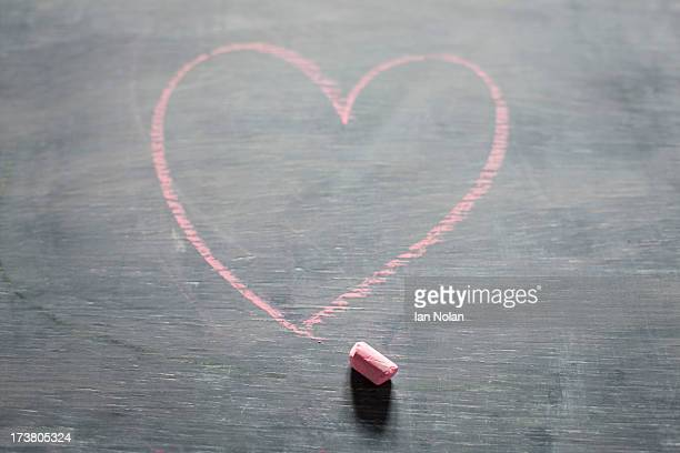 Chalk and heart shape on blackboard