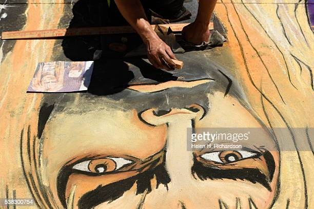 Chalk artist Andrew Leising works on his artwork of David Bowie from the Labyrinth during the 14th annual chalk art festival on June 5 2016 in Denver...