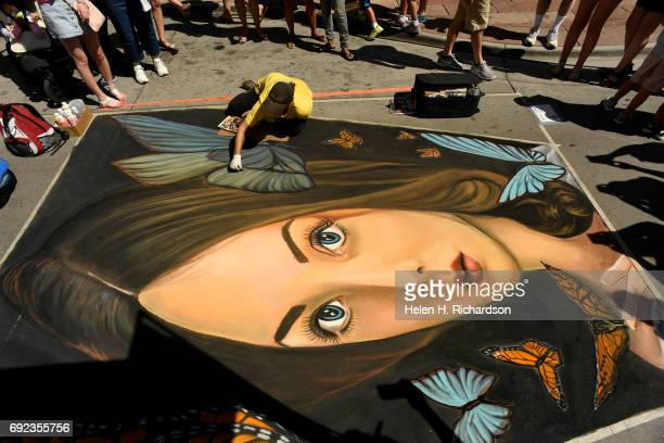 Chalk artist Dawn Morrison Wagner who has taken part in the chalk art festival since it's inception works on her piece entitled Releasing Butterflies...