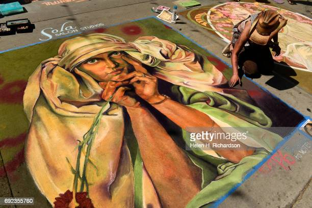 Chalk artist Olivia McLeod works on her piece that was inspired by original artwork by Czech painter Alphonse Mucha during the 15th annual Denver...
