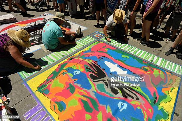 Chalk artists Amy Cheslin left Tom Isaacson middle and Stanley Turner right work on their Chinese Foo Dog inspired chalk art during the 14th annual...