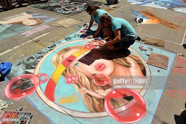 Chalk artists Daniella Battaglioli middle and Misha Farris right work on their piece entitled Map of the Winds by local artist Mark Howell during the...