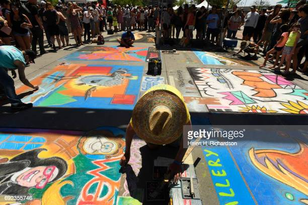 Chalk artists work in the middle of the streets as festival goers can watch as they work from the sidewalks during the 15th annual Denver Chalk Art...