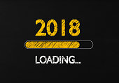 Chalk Drawing: New year 2018 loading on Blackboard. 2018 loading writes on blackboard with a chalk effect. Horizontal composition with copy space.