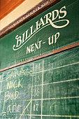 Chalkboard queue for people waiting to play billiards in nightclub.