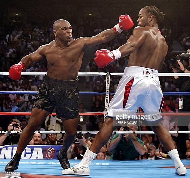 Challenger Mike Tyson of the US swings at Heavyweight Champion Lennox Lewis of England during the 1st round of their World Heavyweight Championship...