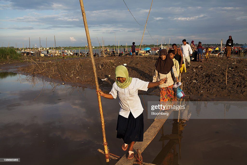 Cham ethnic people cross a footbridge in a fishing community on the Chroy Changvar peninsula in Phnom Penh, Cambodia, on Saturday, Nov. 17, 2012. U.S. President Barack Obama arrives in Phnom Penh later today to join the Association of Southeast Asian Nations (Asean) East Asia Summit, which also includes leaders from Japan, South Korea, India, Russia, Australia and New Zealand. Photographer: Will Baxter/Bloomberg via Getty Images