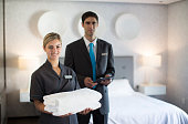 Chambermaid and manager in hotel room