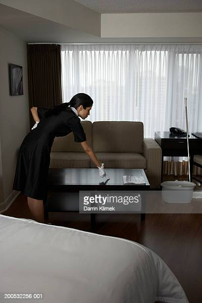 Chambermaid checking for dust on coffee table