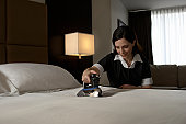 Chambermaid ironing sheet on bed