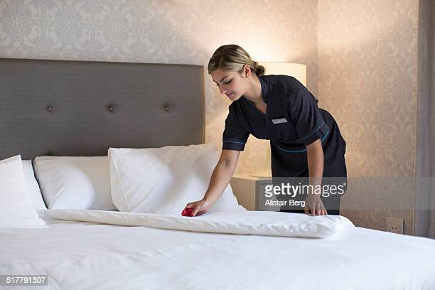 Chambermaid making bed in hotel room
