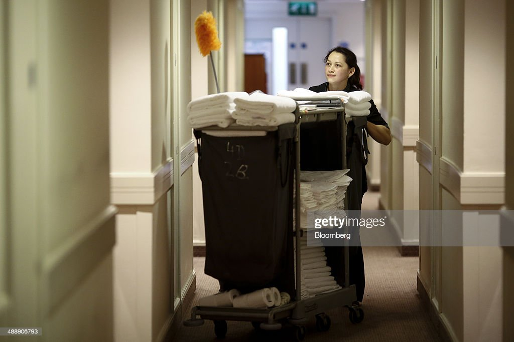 A Chambermaid Pushes Cleaning Trolley Along Room Corridor In This Arranged Photograph Taken Inside