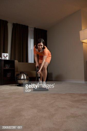 Chambermaid vacuuming hotel room floor : Stock Photo