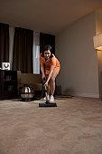 Chambermaid vacuuming hotel room floor