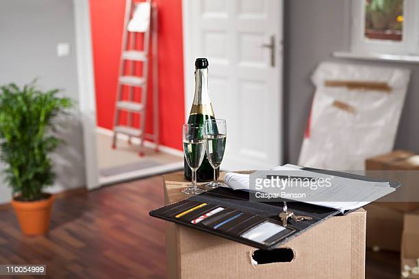 Champagne and a contract in a living room with moving boxes
